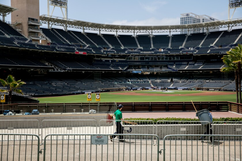 Padres players take batting practice at Petco Park on Tuesday as maintenance crews do their work.
