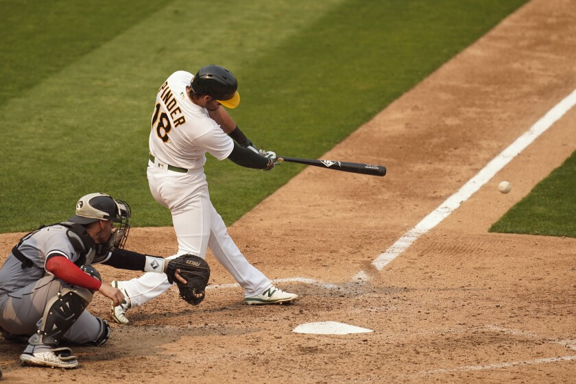 Oakland Athletics' Chad Pinder (18) hits a two-run single in front of Chicago White Sox catcher Yasmani Grandal during the fifth inning of Game 3 of an American League wild-card baseball series Thursday, Oct. 1, 2020, in Oakland, Calif. (AP Photo/Eric Risberg)