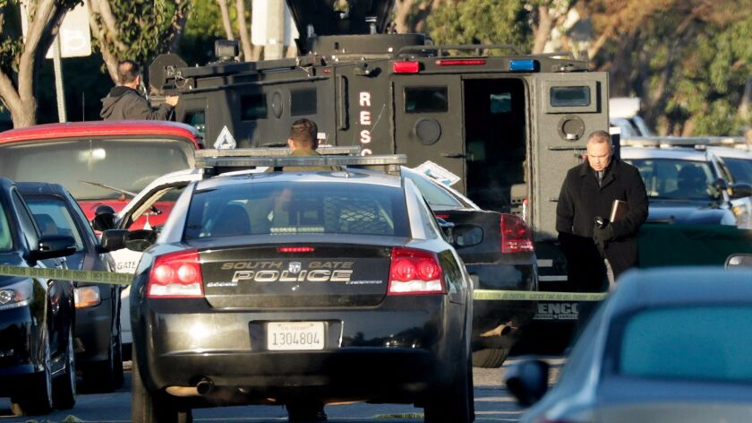 Authorities investigate the scene of a police shooting that left a suspect dead in the 2700 block of Illinois Avenue in South Gate on Nov. 28.