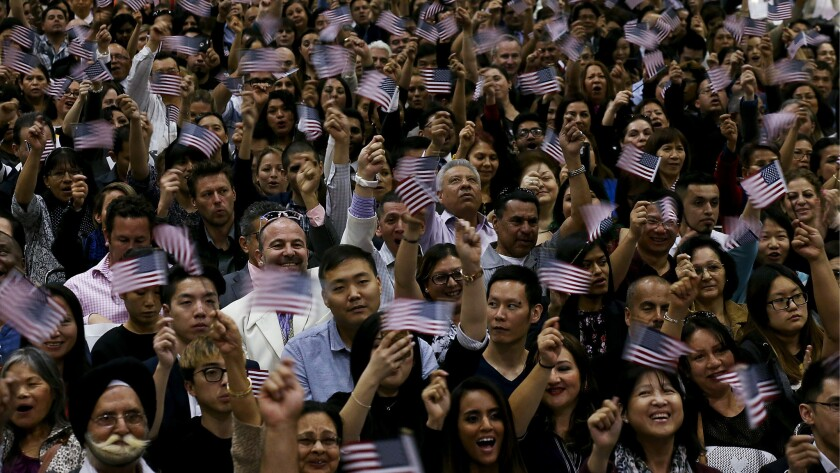 Newly sworn-in Americans wave flags after taking the oath of citizenship.