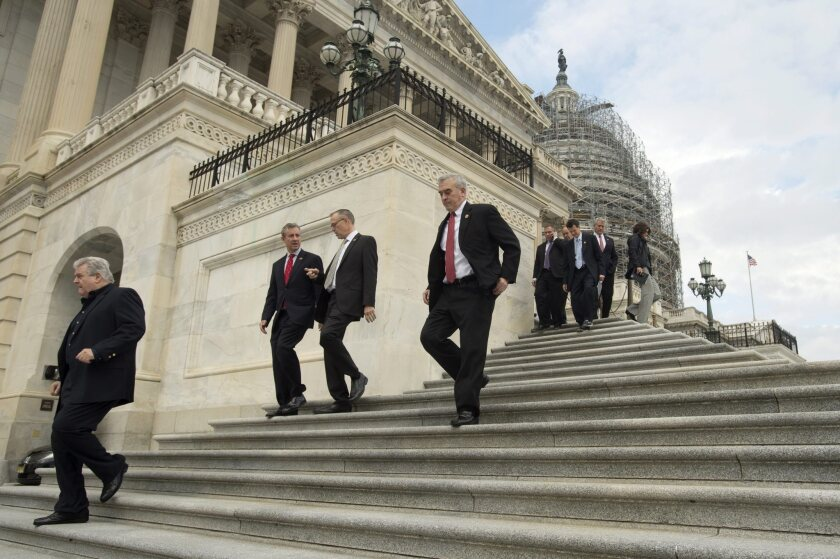 Members of Congress and aides walk down the steps of the Capitol after passing a massive budget measure in the last scheduled vote of the year.