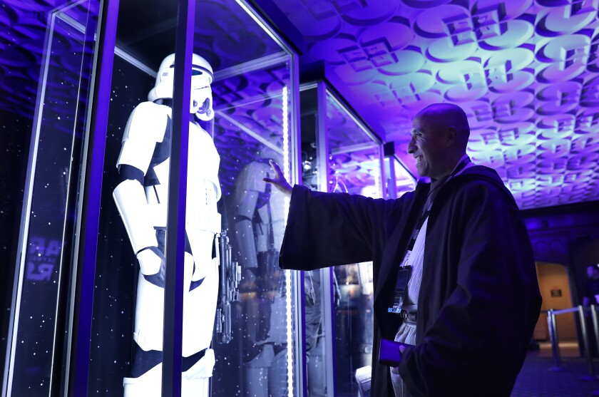 """Christopher Duarte, 55, of Barstow, checks out a costume exhibit during a """"Star Wars"""" marathon at the El Capitan Theatre in Hollywood, culminating in the premiere of """"The Rise of Skywalker"""" on Thursday, December 19, 2019."""