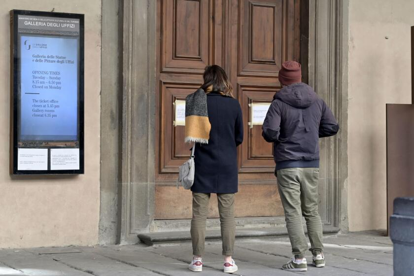 Two people look at a door to Italy's Uffizi, where a sign announcing its closure is posted.