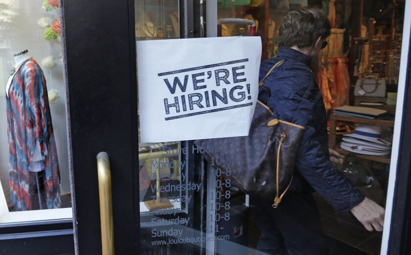 """In this Wednesday, May 18, 2016, photo, a woman passes a """"We're Hiring!"""" sign while entering a clothing store in the Downtown Crossing of Boston. On Thursday, May 26, 2016, the Labor Department reports on the number of people who applied for unemployment benefits the week before. (AP Photo/Charles"""