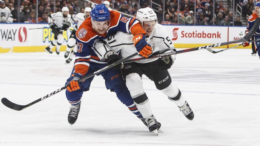 Los Angles Kings' Austin Wagner (51) and Edmonton Oilers' Matthew Benning (83) race for the puck dur