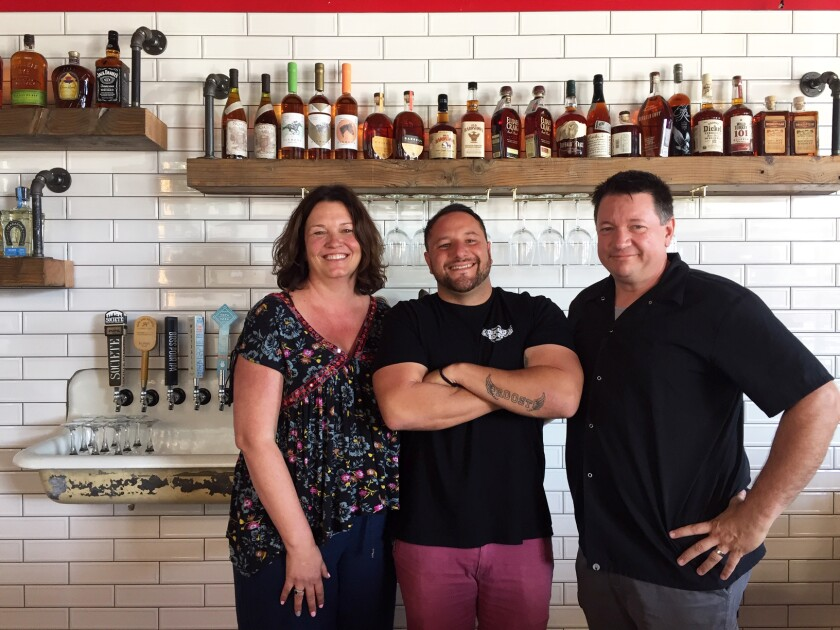 """Bantam's Roost Public House partners Aaron Browning, left, her husband Roger """"Roddy"""" Browning, right, and Alex Kleinman, center, whose devotion to the new pub can be seen in the tattoo on his forearm."""