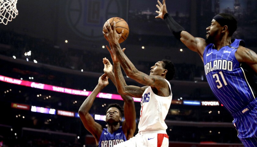 Clippers guard Lou Williams splits the defense of Magic forward Terrence Ross (31) and center Mo Bamba for a layup Sunday.
