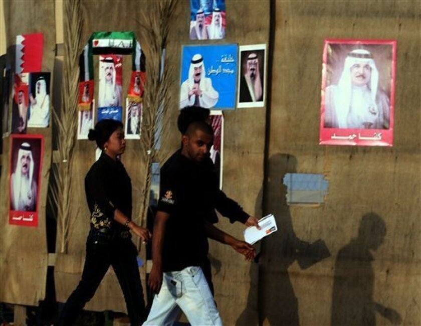 Pedestrians pass by a construction site Tuesday, May 31, 2011, in Manama, Bahrain, with barricades decorated with images of Bahraini, Saudi and Emirati leaders. Bahrain's Justice Ministry warned Tuesday that authorities will not ease pressure on anti-government groups after emergency laws are removed even as the nation's king appealed for a dialogue beginning in July. (AP Photo/Hasan Jamali)