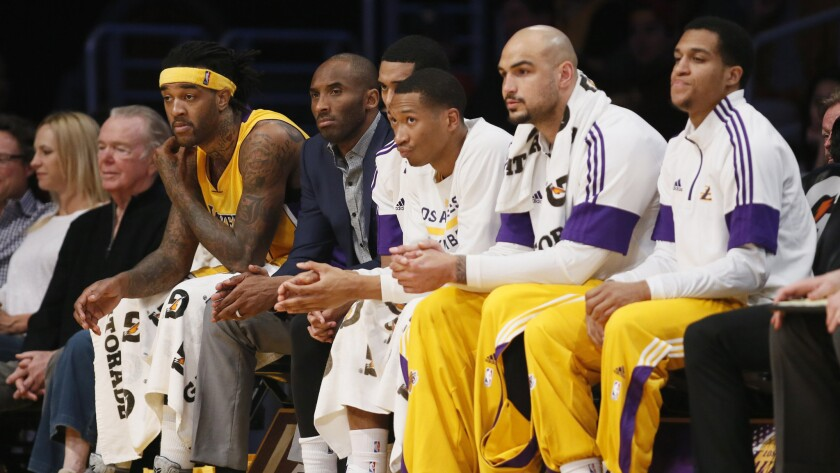 Injured Lakers star Kobe Bryant, second left, sits with his teammates on the bench during a win over the Detroit Pistons at Staples Center on March 10.