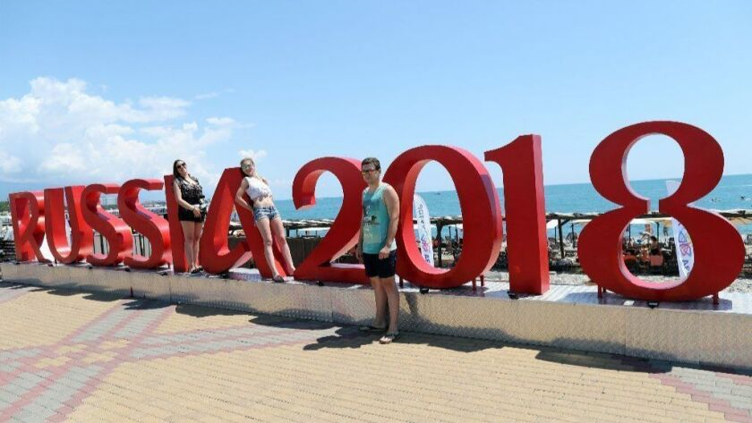 Soccer fans pose next to World Cup sign near Sochi stadium in Sochi, Russia.