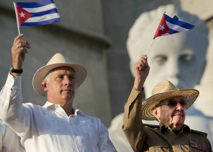 FILE - In this May 1, 2019 file photo, Cuba's President Miguel Diaz-Canel, left, and former Cuban President Raul Castro wave Cuban flags as they watch the annual May Day parade file past at Revolution Square in Havana, Cuba. President Diaz-Canel has blamed the administration of U.S. President Donald Trump for the present energy crisis that is facing Cuba. (AP Photo/Ramon Espinosa, File)