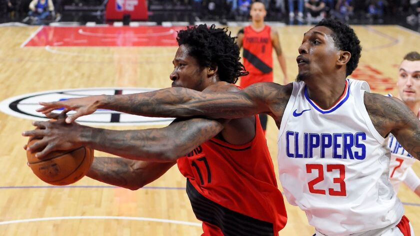 Clippers guard Lou Williams and Portland forward Ed Davis reach for a rebound on Jan. 30.