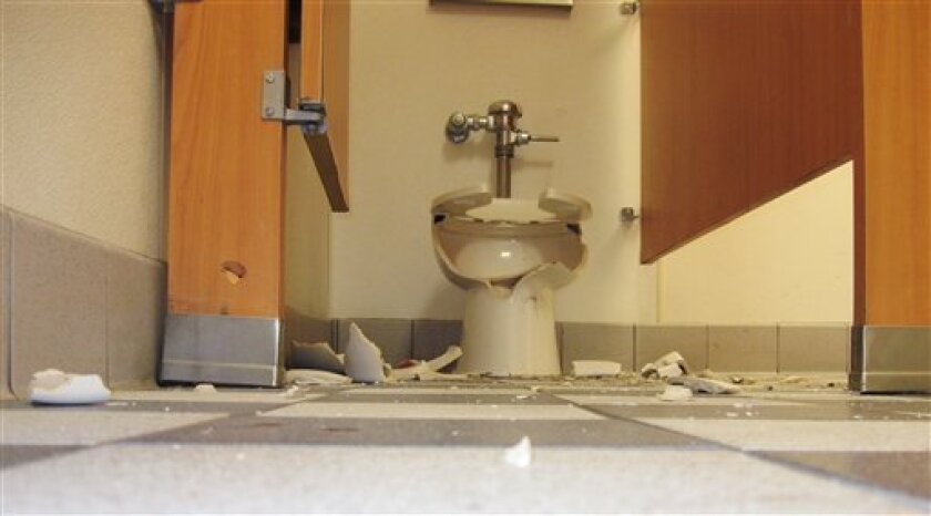 In this photo released by the Centerville Police Dept. shows a shattered toilet in the restroom a Carl's Jr. restaurant Tuesday in Centerville, Utah Tuesday Jan. 13, 2009. Police say a man's gun fell out of its holster while he pulled up his pants after using the bathroom at a Carl's Jr. restaurant