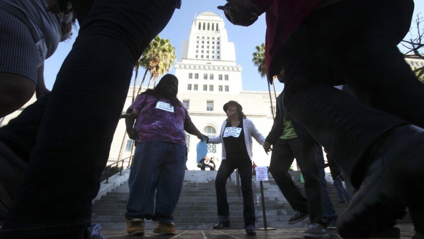 A group of community activists protest on the steps of Los Angeles City Hall in December. Protesters say a new zoning plan does too little to protect affordable housing.