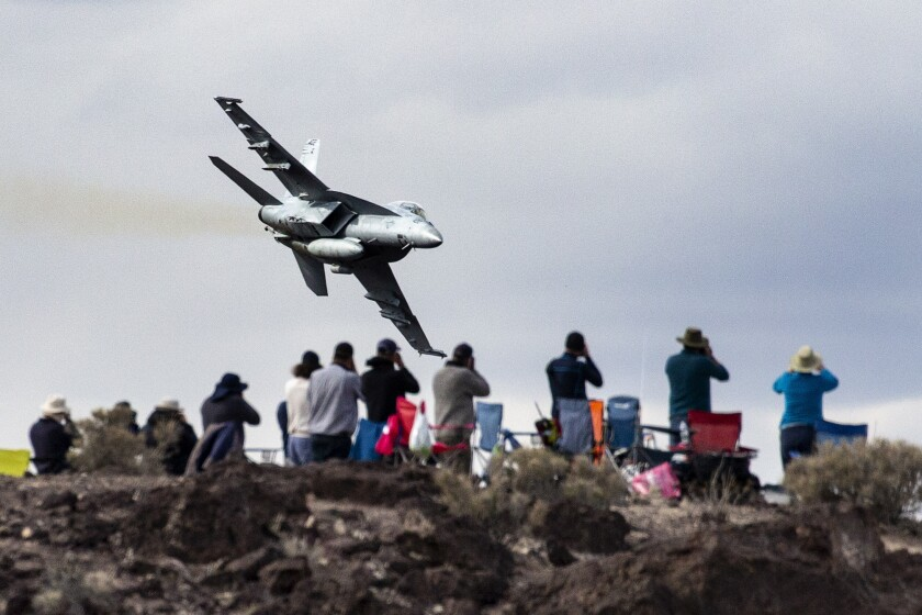 """Photographers train their cameras on an F-18 fighter jet from Lemoore Naval Air Station, Calif., diving into Rainbow Canyon. Air Force and Navy fighter jets train in Rainbow Canyon, known to many as """"Star Wars Canyon,"""" near the western edge of Death Valley National Park."""