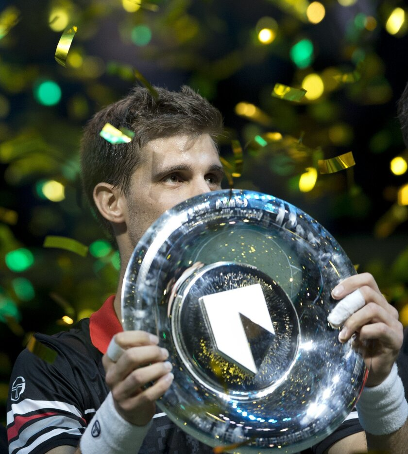 Slovakia's Martin Klizan holds the trophy after winning the ABN AMRO world tennis tournament against France's Gael Monfils in three sets 6-7 (1-7), 6-3, 6-1, at the Ahoy arena in Rotterdam, Netherlands, Sunday, Feb. 14, 2016. (AP Photo/Peter Dejong)