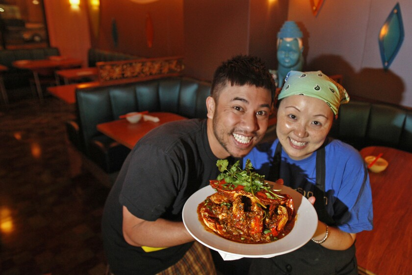 Nguyen Tran and his wife, chef Thi Tran, hold a dish of Singaporean chile crab at Starry Kitchen when it was a pop-up restaurant in Tiara Cafe.