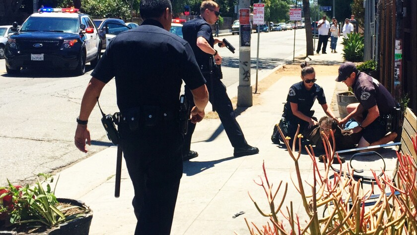 Los Angeles police subdue a man on Monday afternoon in Venice while responding to a report of a man armed with a knife in the 600 block of Rose Avenue.