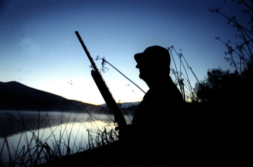 In the pre-dawn light on the banks of the Upper Otay Reservoir, a hunter for ducks to approach the area so he can have a shot at them.