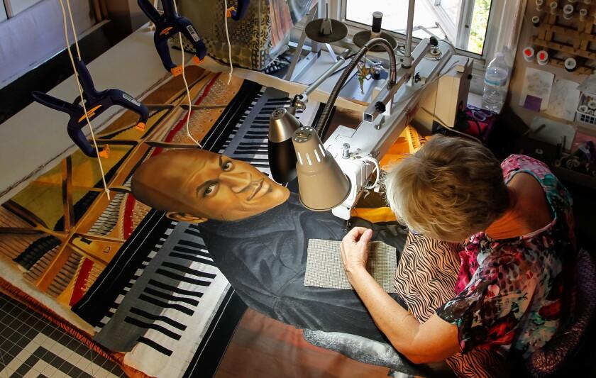 Artist Linda Anderson works on her art quilt based on a photo of jazz musician Joshua White by Union-Tribune photographer Eduardo Contreras.