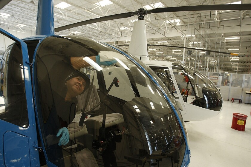 A technician wipes the window of an R44 helicopter at Robinson Helicopter Co.'s factory in Torrance.