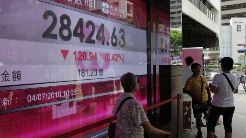 People walk past a bank electronic board showing the Hong Kong share index at Hong Kong Stock Exchan