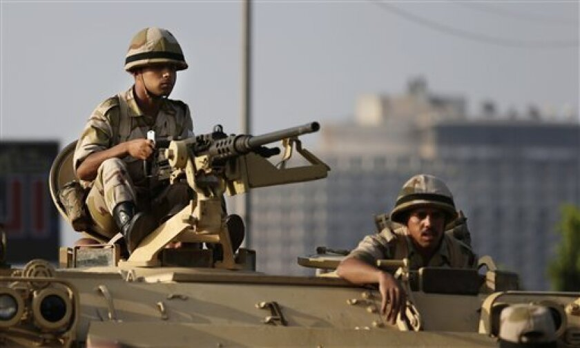 Egyptian army soldiers take their positions on top of their armored vehicle to guard the entrances of Tahrir square, in Cairo, Egypt, Monday, July 8, 2013. Egyptian military officials said gunmen killed at least five supporters of the former president when people tried to storm a military building in Cairo. The official, who declined to be named because he was not authorized to brief reporters, also said a group had tried to storm the headquarters of the Republican Guard. He added that those kil