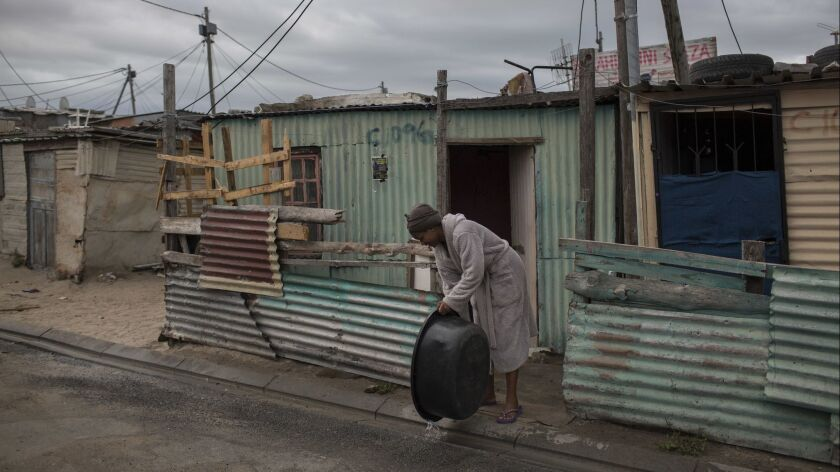 In this Friday, Feb. 2, 2018 photo a woman throws away used water in an informal settlement near Cap