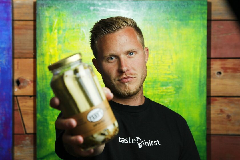 Jarod Farver, seen with his artwork behind him, is the man behind Farv's Pickles. Growing up in Topeka, Kansas, both sides of Farver's family were avid picklers. But it wasn't until a Super Bowl party a couple years back that he took a stab at making them himself.