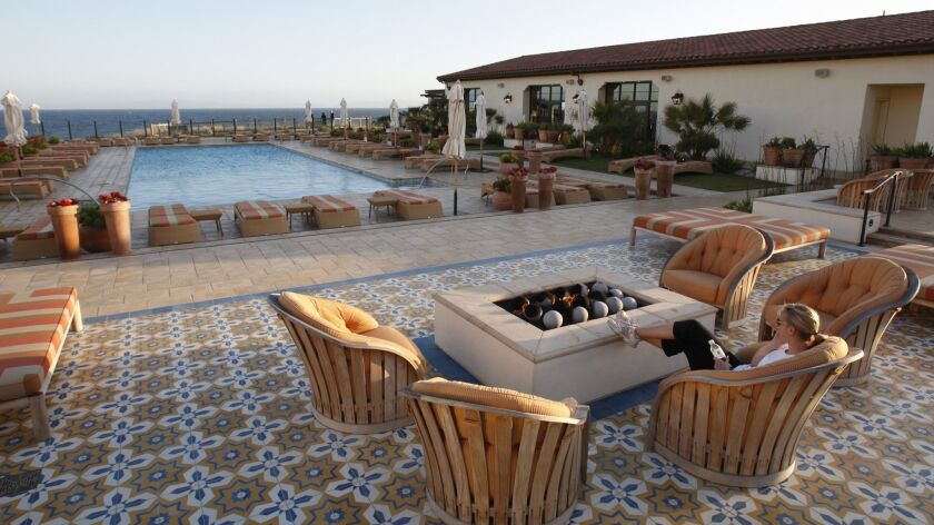 A woman relaxes by the fire pit overlooking the swimming pool and ocean at sunset at the Terranea Resort in Rancho Palos Verdes. Unite Here Local 11 is intensifying its call for a boycott of the resort over allegations of sexual assaults on workers.