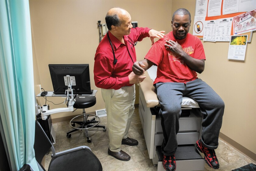 Dr. James Jackson performs a physical on Matthew Shorter, 51, a Medicaid patient enrolled in the Healthy Indiana Plan, at the Heart City Health Center in Elkhart.
