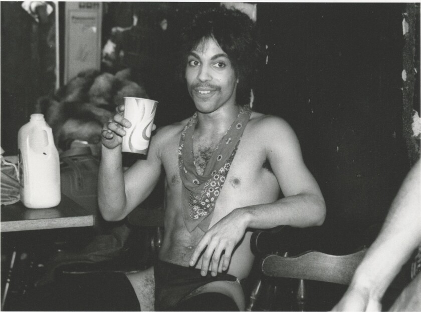 "Prince sips orange juice backstage during the 1981 Dirty Mind tour, featured in ""The Beautiful Ones."""