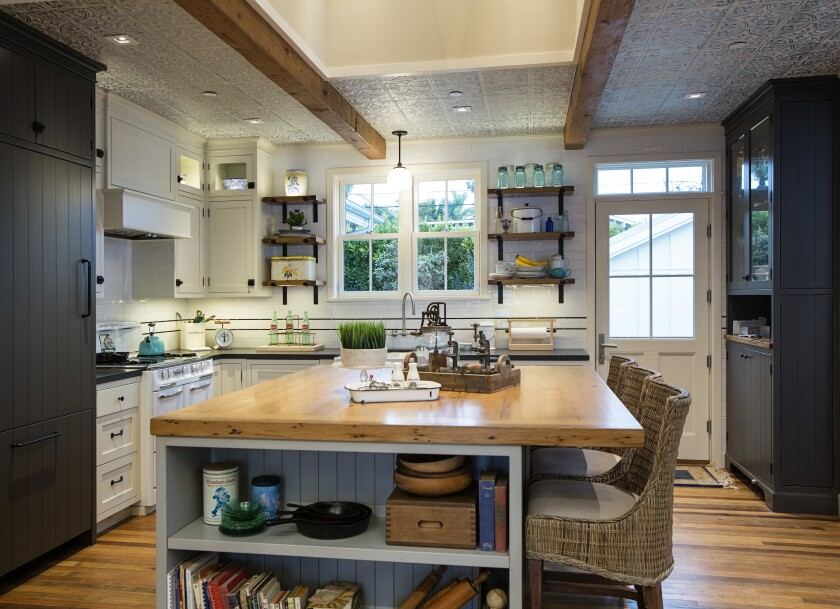 The kitchen's skylight provides natural light from a dormer window. The skylight is set off against antiqued tin ceiling tiles and vintage beams. The 1950s Wedgewood stove, in the left corner, was the impetus for the whole farmhouse project.