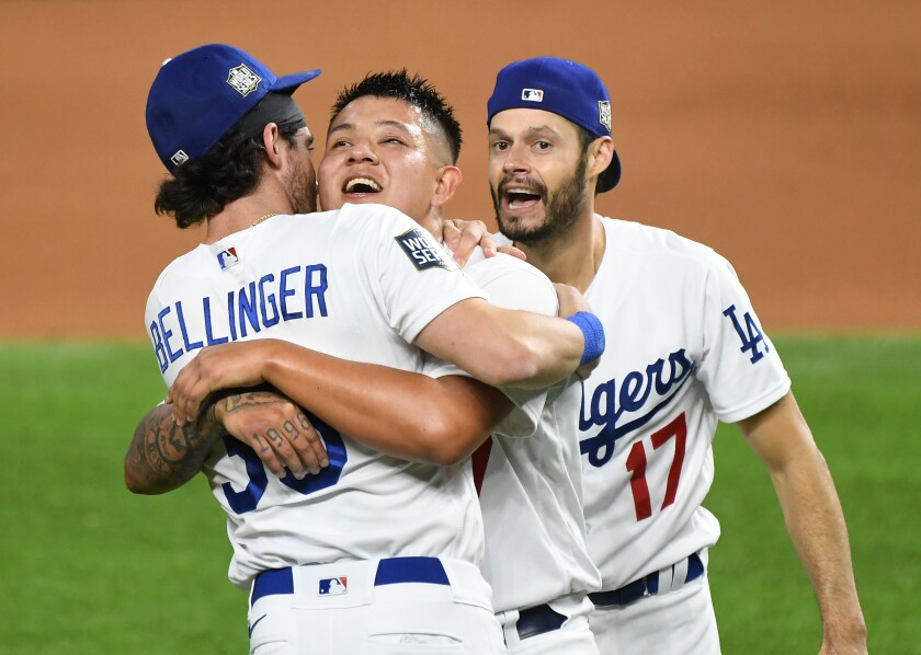 Dodgers pitcher Julio Urías celebrates with Cody Bellinger and Joe Kelly.