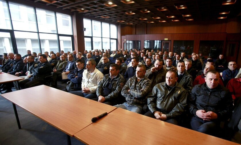 Defendants, their lawyers and police officers sit in the front rows in a courtroom of the criminal court in Skopje, Macedonia, Tuesday, Feb. 9, 2016. The trial opens Tuesday for 29 people charged in connection with a 2015 shootout with police in the northern Macedonian town of Kumanovo that left 18