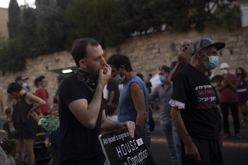 Shachar Oren, 25, whistles during a protest against Israel's Prime Minister Benjamin Netanyahu outside his residence in Jerusalem, Tuesday, Aug. 4, 2020. The boisterous rallies against Netanyahu have brought out a new breed of first-time protesters -- young, middle-class Israelis who have little history of political activity but feel that Netanyahu's scandal-plagued rule and his handling of the coronavirus crisis have robbed them of their futures. (AP Photo/Maya Alleruzzo)