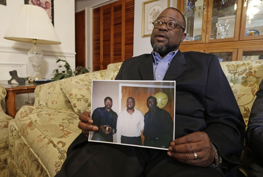 Anthony Scott holds a photo of himself, center, and his brothers Walter Scott, left, and Rodney Scott, right, as he talks about his brother at his home near North Charleston, S.C.