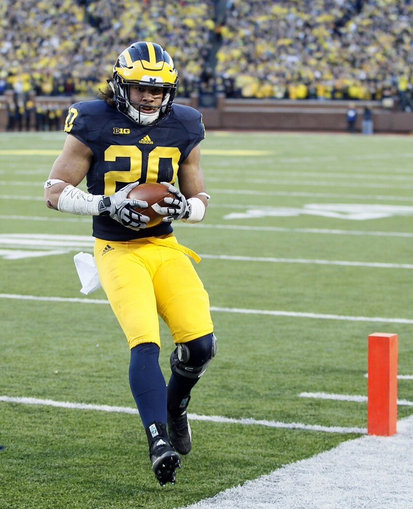 Michigan's Drake Johnson scores against Rutgers on a 1-yard run during the first half of an NCAA college football game Saturday, Nov. 7, 2015, in Ann Arbor, Mich. Michigan defeated Rutgers 49-16. (AP Photo/Duane Burleson)