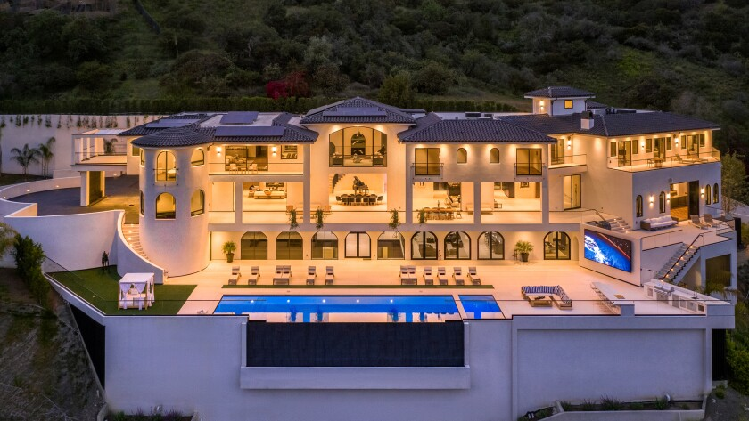 A large, white mansion in the hills of Bel-Air with a deck and infinity pool