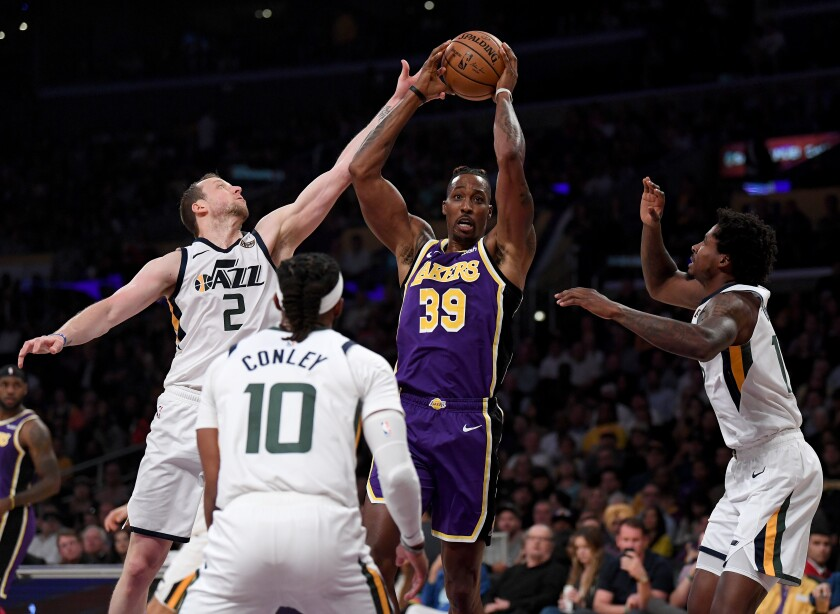 Lakers' Dwight Howard (39) grabs a rebound in front of Utah Jazz's Ed Davis (17) and Mike Conley (10), as he is fouled by Joe Ingles (2), during the first half at Staples Center on Friday.