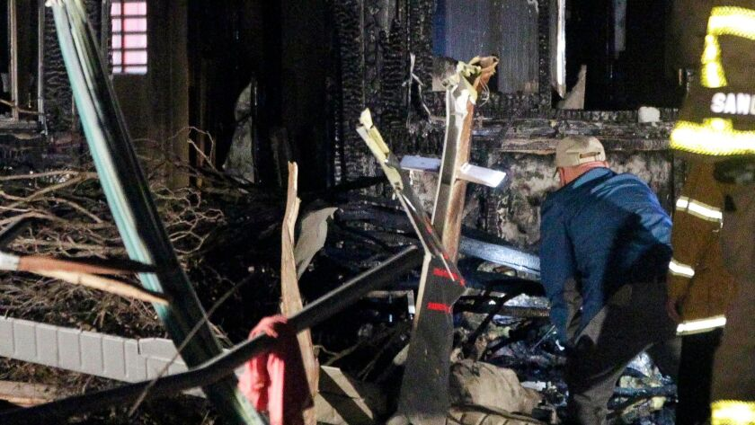 An investigator standing next to the tail section looks at the charred remains of a small plane that crashed into a house in San Diego.
