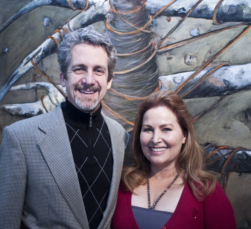 ". Artist Lauren Carrera poses with her husband, Chris Schuck, head of La Jolla Country Day School, in front of one of her pod paintings. ""He's my installer, and my staff,"" she said. Photos by Maurice Hewitt"