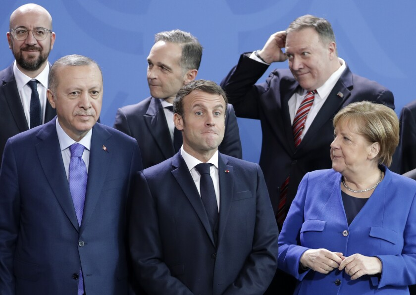 FILE - In this Sunday, Jan. 19, 2020 file photo, German Chancellor Angela Merkel, front right, speaks with French President Emmanuel Macron, front center, and Turkish President Recep Tayyip Erdogan during a group photo at a conference on Libya at the chancellery in Berlin, Germany. A festering row between France and Turkey over a naval standoff in the Mediterranean Sea has shone a glaring searchlight on NATO's struggle to keep order among its ranks and exposed weaknesses in a military alliance that can only take action by consensus. (AP Photo/Michael Sohn, File)