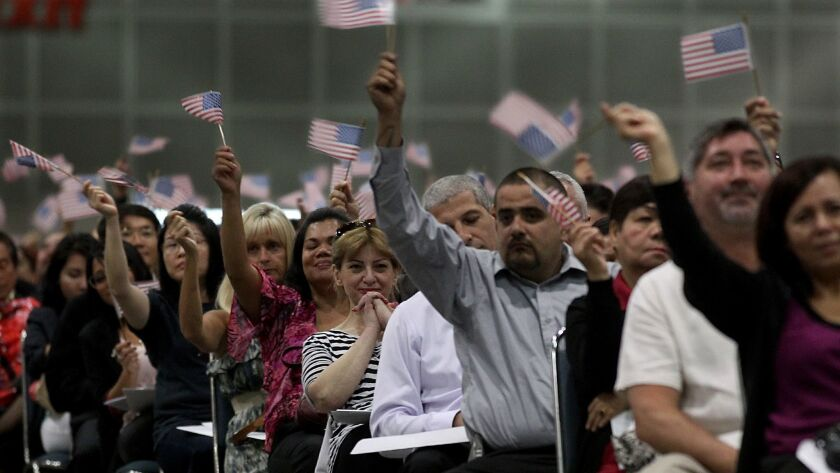 LOS ANGELES, CALIF. - AUG. 21, 2013. Some 4,000 new Amerivcan citizens wave small American flags as