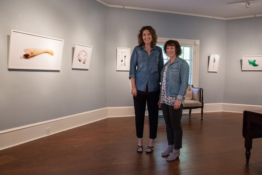 Jody Servon, left, and Lorene Delany-Ullman, right, pose for a photograph with the exhibit at the Horace Williams House in Chapel Hill, N.C. in October 2017.