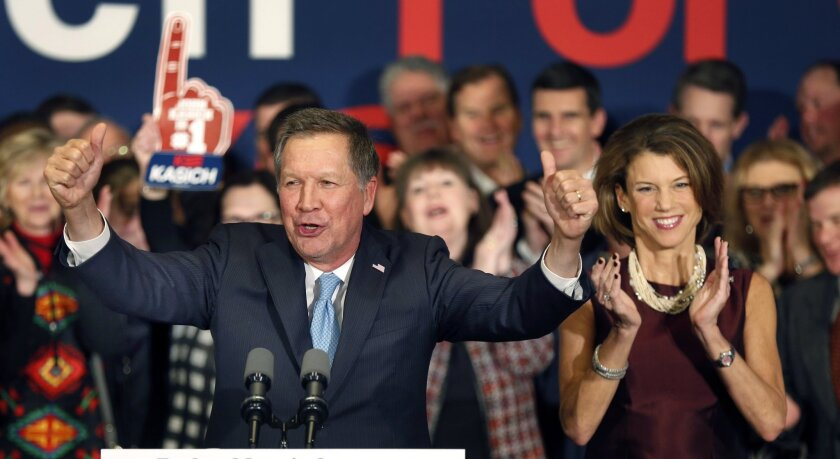 With his wife Karen at his side Republican presidential candidate Gov. John Kasich of Ohio cheers with supporters Tuesday in Concord, N.H., at his primary night rally.