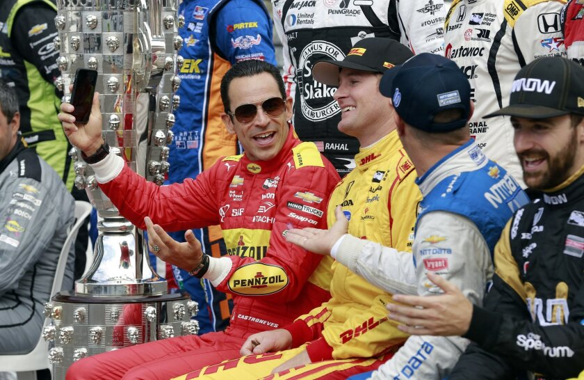 Helio Castroneves, left, jokes with Ryan Hunter-Reay, center, and Tony Kanaan during a photo of the starting field before the final practice session for the Indianapolis 500 auto race at Indianapolis Motor Speedway in Indianapolis, Friday, May 27, 2016. (AP Photo/R Brent Smith)