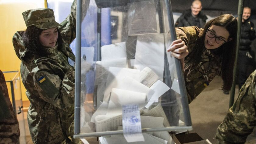 Ukrainian government soldiers, members of the local election commission, open a ballot box in a tent