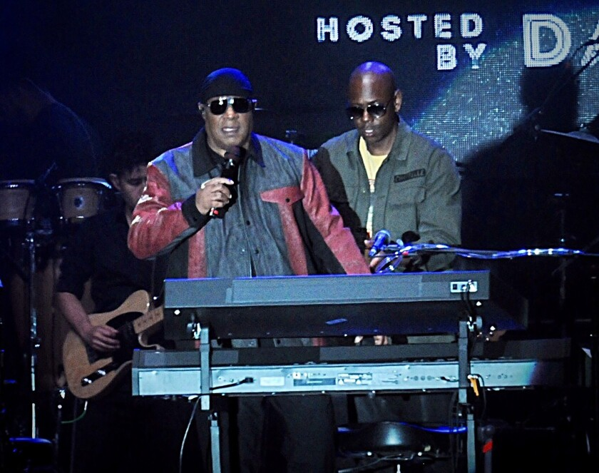 Musician Stevie Wonder, front left, and comedian Dave Chappelle appear on stage during the Gem City Shine event