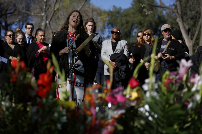 Raquel Salinas takes part in the ceremony at the site of a mass grave in the Los Angeles County Crematory and Cemetery on Wednesday.